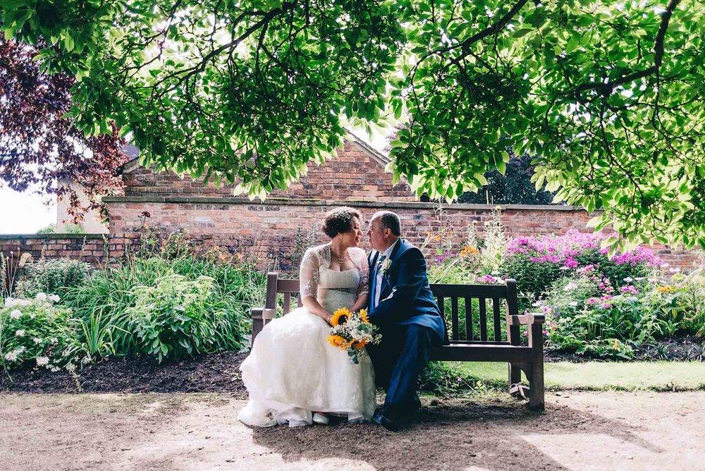 Bride and groom backlit in didsbury parsonage gardens