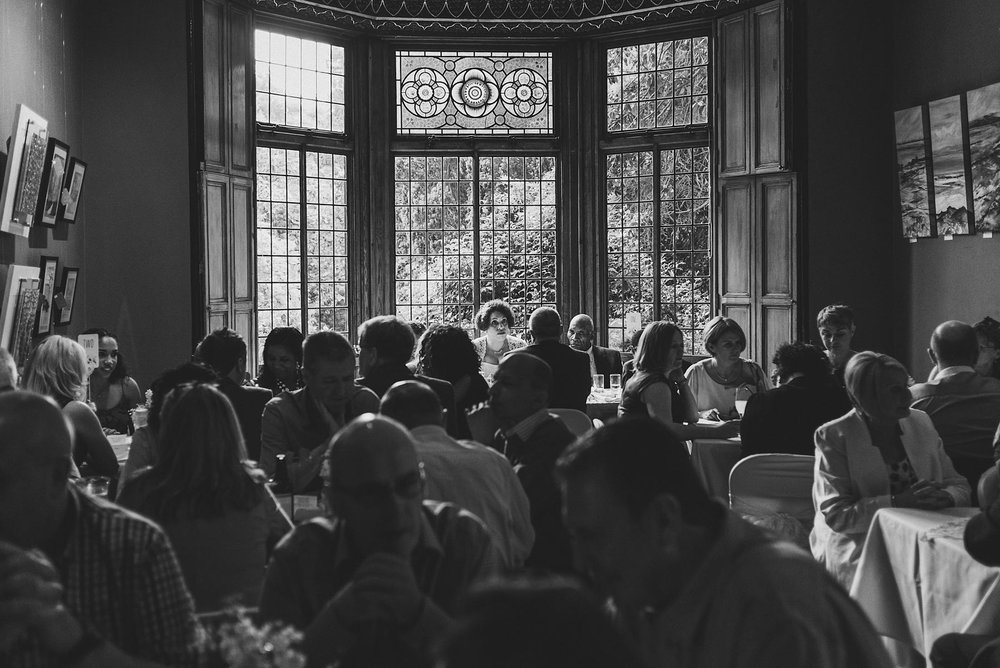 Black and white image of light coming through windows and enveloping the bride