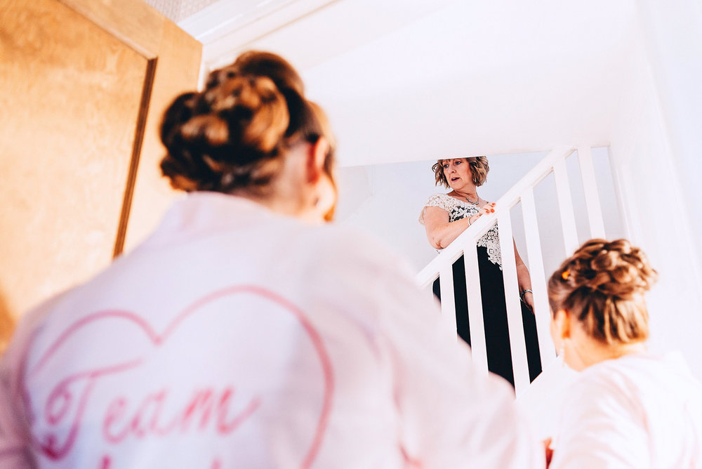 Mother of the bride goes upstairs to help the bride get ready