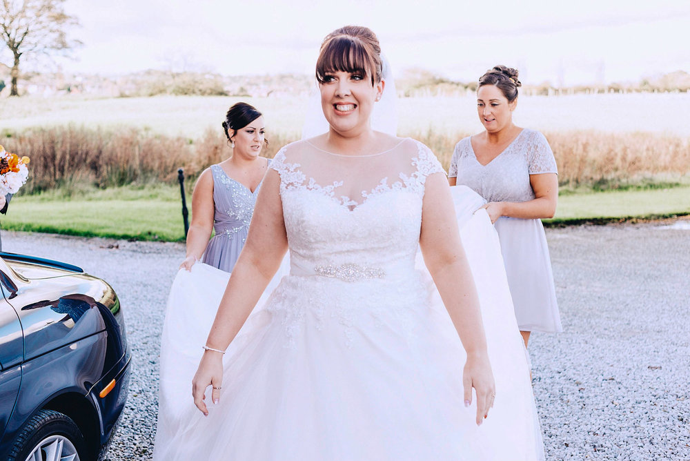 Bride looks happy while bridesmaids hold her dress