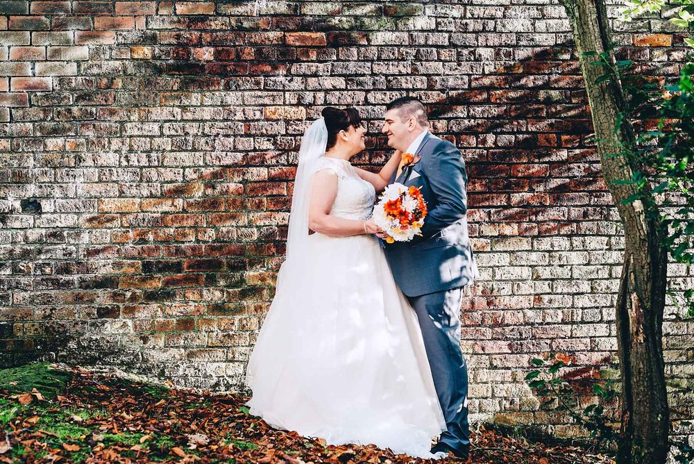 Bride and groom pose for a photo while light hits wall behind them