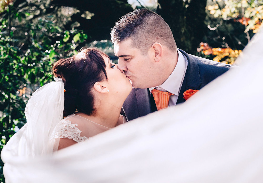 Bride and groom kiss while veil blows across them