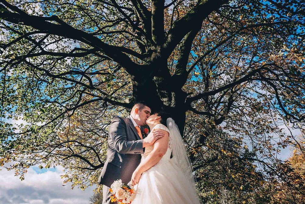 Bride and groom kiss underneath large tree