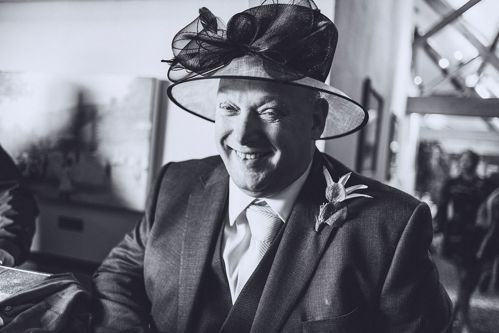 Father of the Bride wears wife's hat and laughs