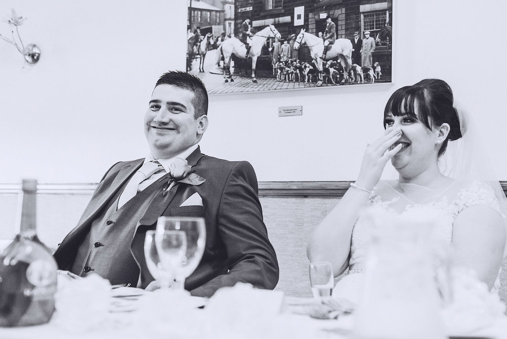 Bride and groom laugh at speech