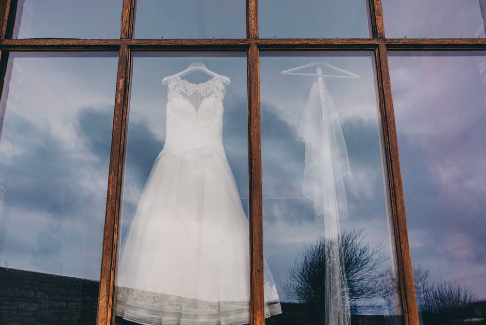 Brides dress hung up against window with clouds reflected in glass