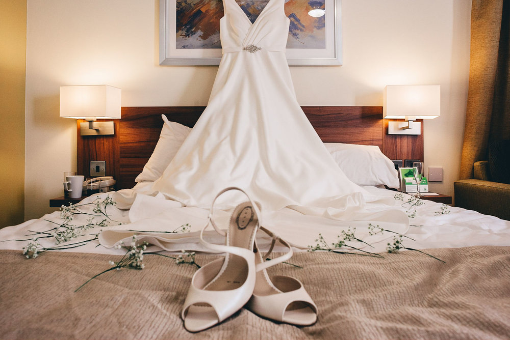 Wedding dress draped on bed on the morning of the wedding