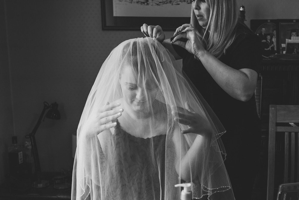 Black and white image of bride's veil being placed by hairdresser