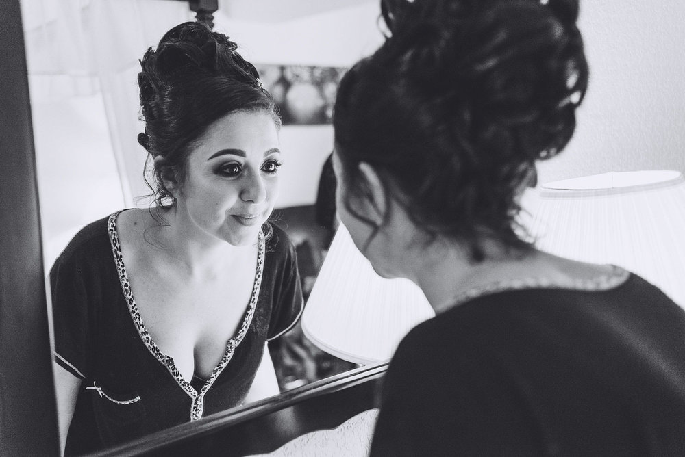 Bride smiles while looking in mirror