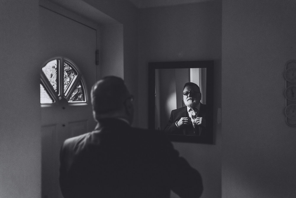 Dramatic black and white image of Father of the bride adjusts tie in mirror