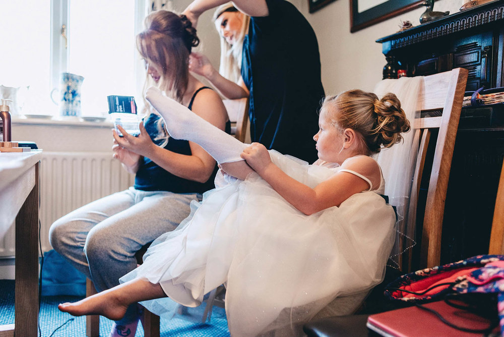 Young bridesmaid pulls on her socks