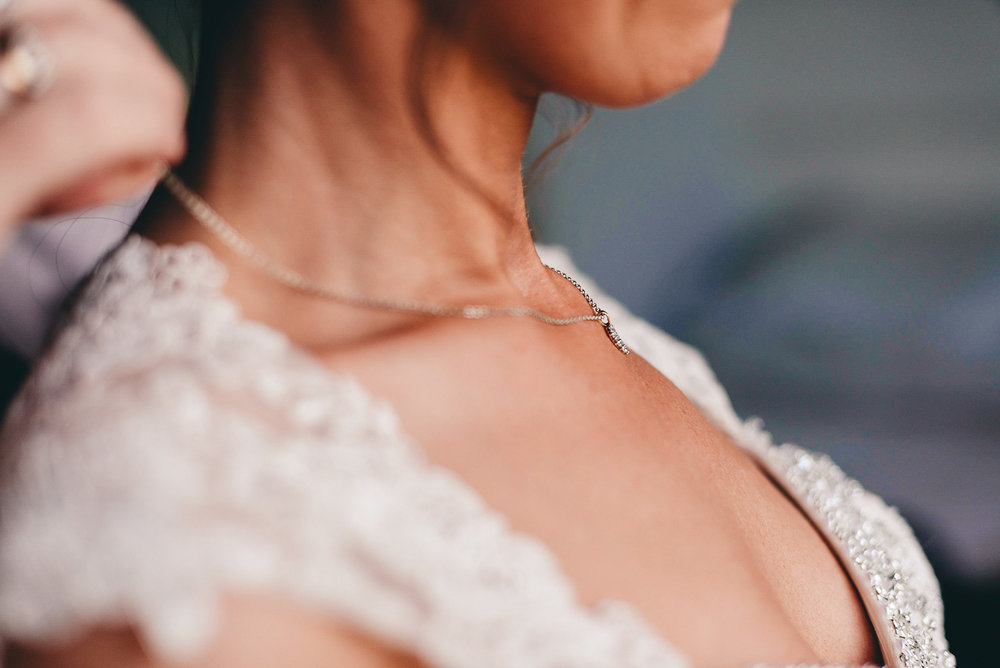 Bride has a neckless placed around her neck