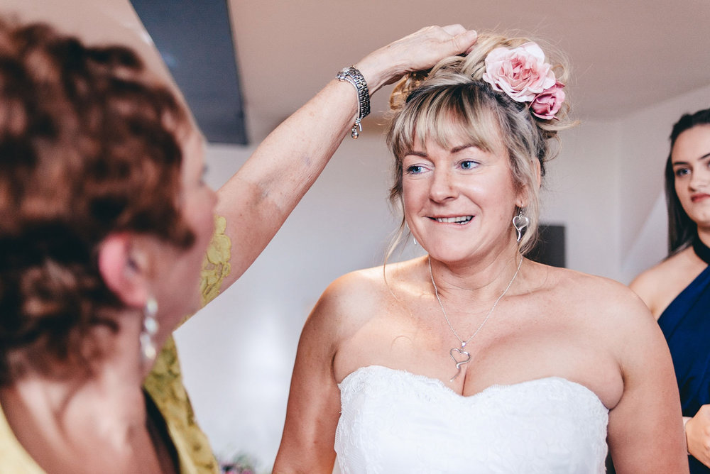 Mother of the bride helps daughter with hair