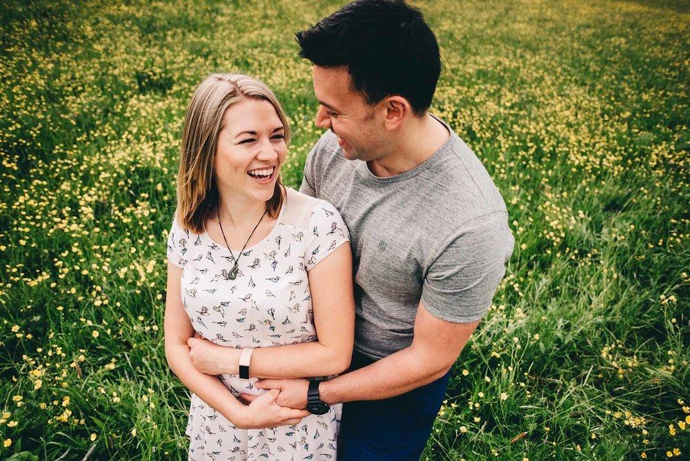 Engaged couple look loving at each other in Holmebrook Valley Park in Spring