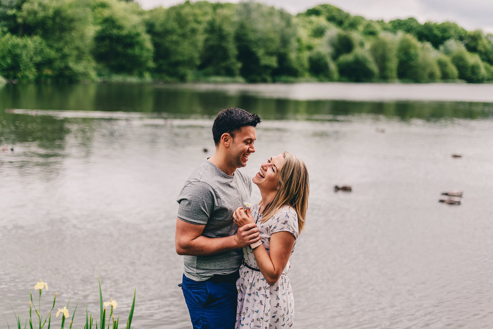 Engaged couple pose in front of lake during engagement shoot