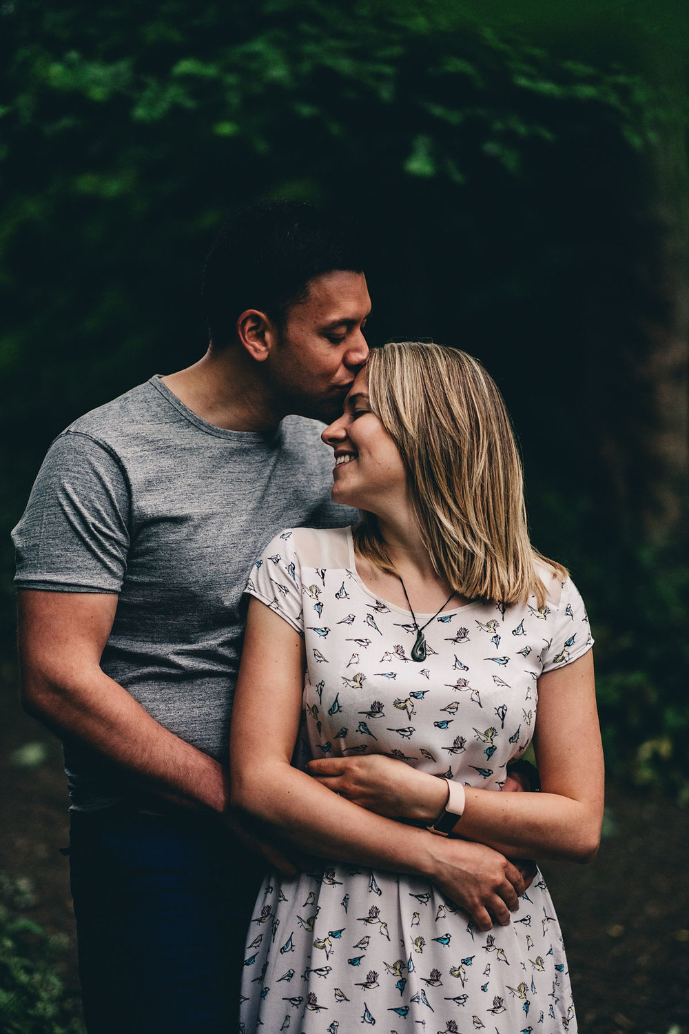 Couple kiss during engagement shoot in Holmebrook Valley Park, Chesterfield
