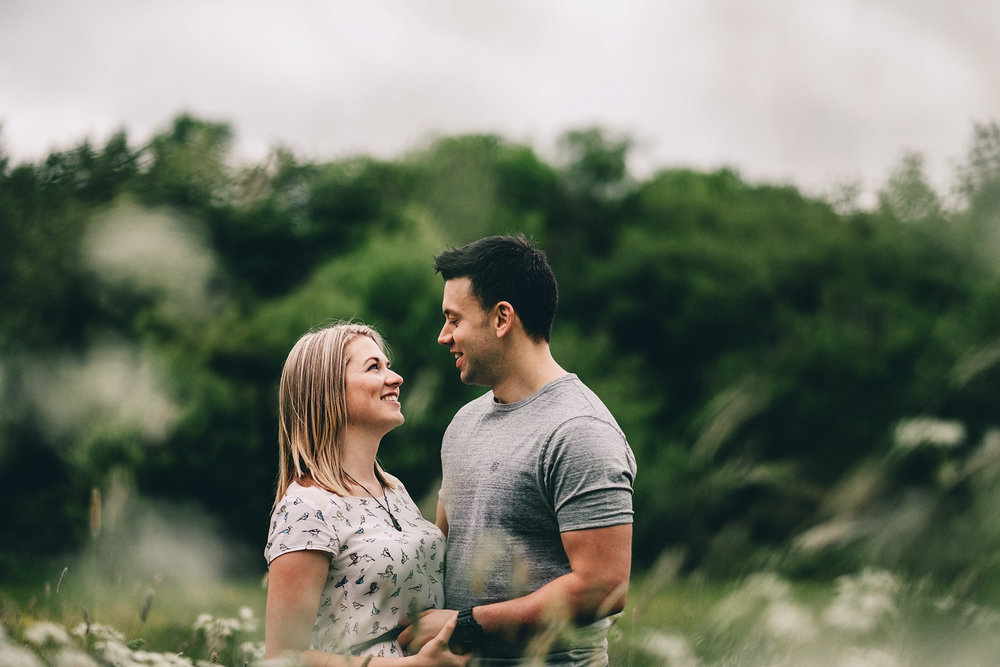 Couple pose in field during spring in Holmebrook Valley Park, Chesterfield