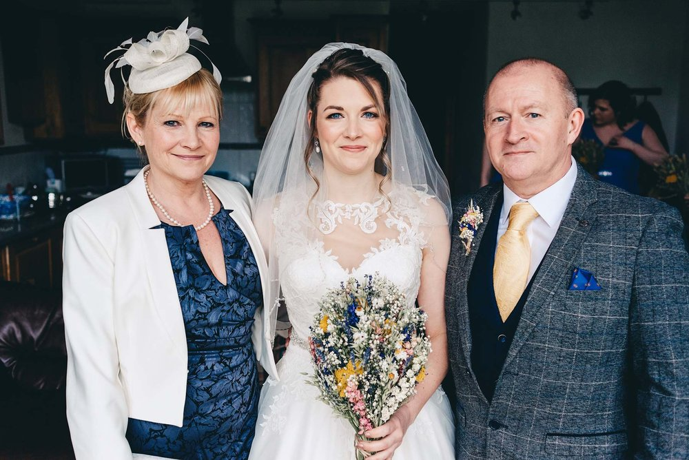 Bride poses with mother and father on the morning of the wedding in Rosedew Farm Llantwit Major south Wales