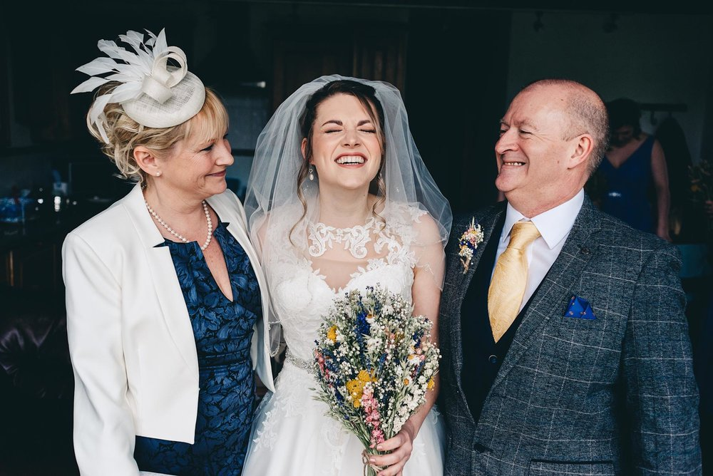 Bride laughs with mother and father on the morning of the wedding in Rosedew Farm Llantwit Major south Wales