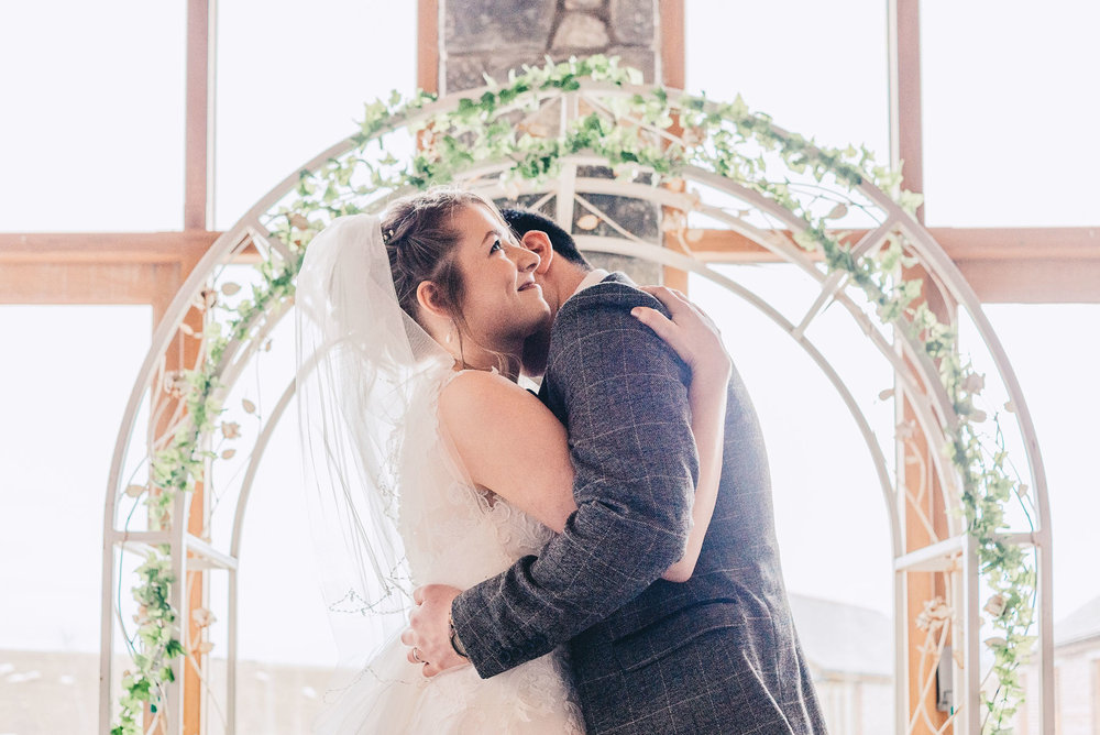 Bride and Groom hug during wedding service at Rosedew Farm, Llantwit Major, South Wales