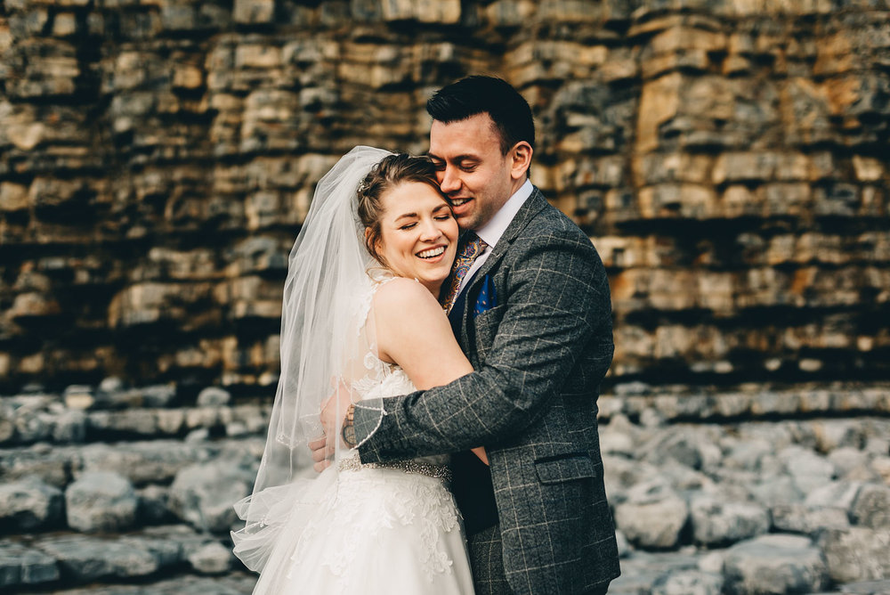 Couple just married hug by cliffs at Llantwit Major, South Wales