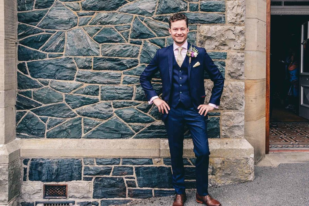 Groom poses outside ceremony venue