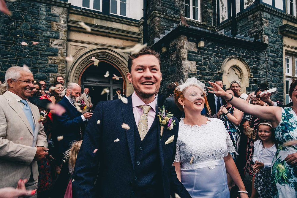 Bride and groom smile after confetti