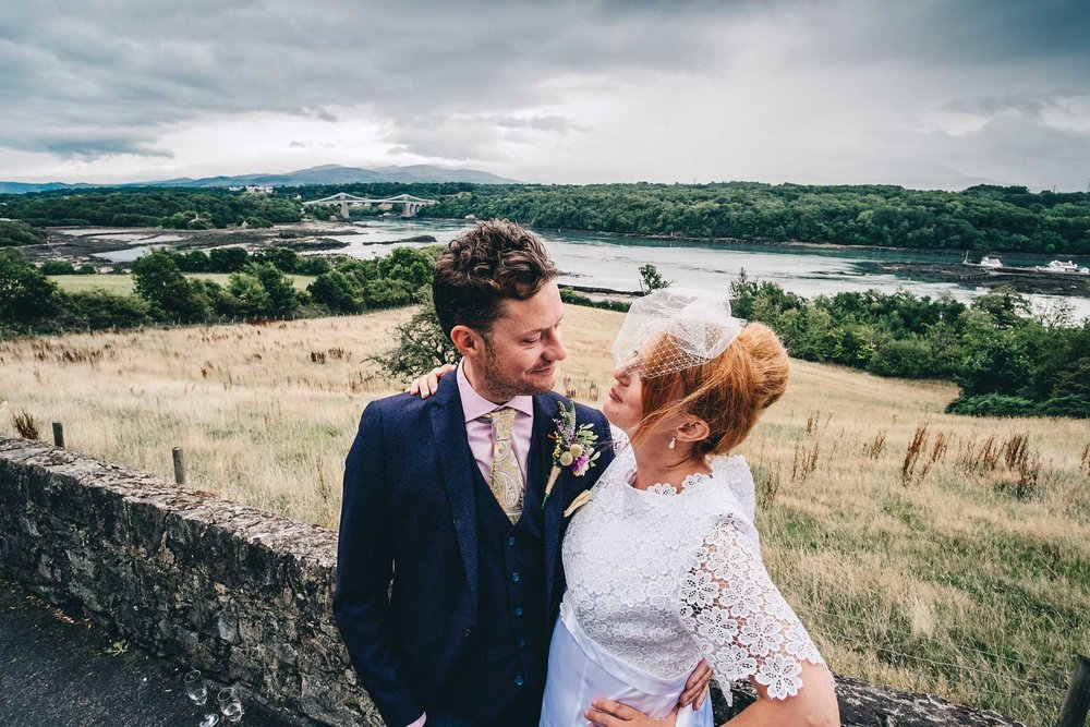 Bride and groom look lovingly at each other at The Menai Bridge Viewpoint in Anglesey