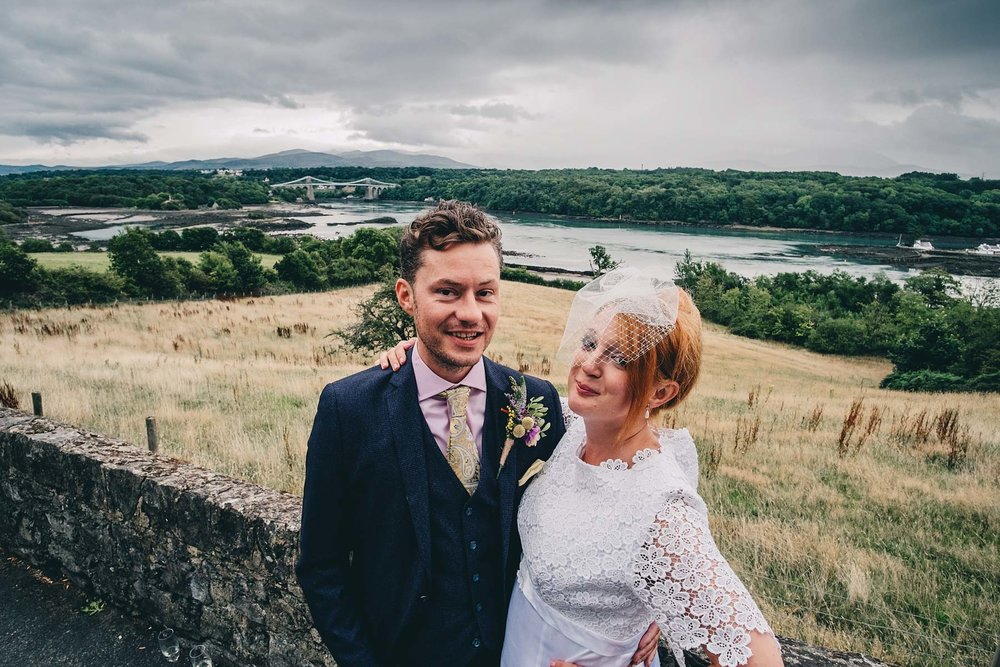 Bride and groom look at camera while posing at The Menai Bridge Viewpoint in Anglesey