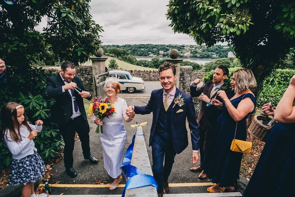 Bride and groom walk up steps while guests blow bubbles at Hugh Owens Hall