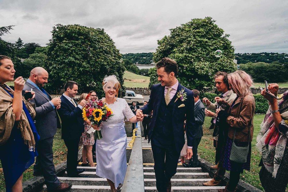 Bride and groom walk up steps of Bangor University