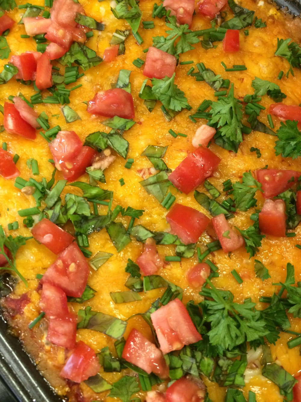 Taco dip garnished with fresh herbs and veggies.
