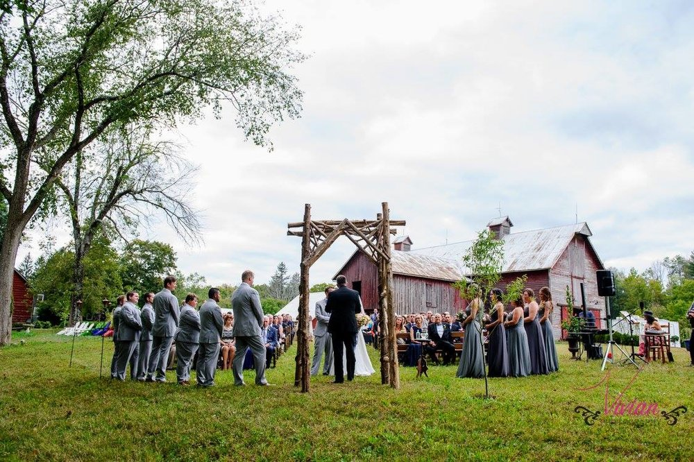 bridal-couple-standing-under-arbor-with-barn-in-background.jpg