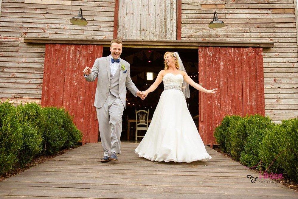 bride-and-groom-posing-outside-rustic-barn-wedding-venue.jpg