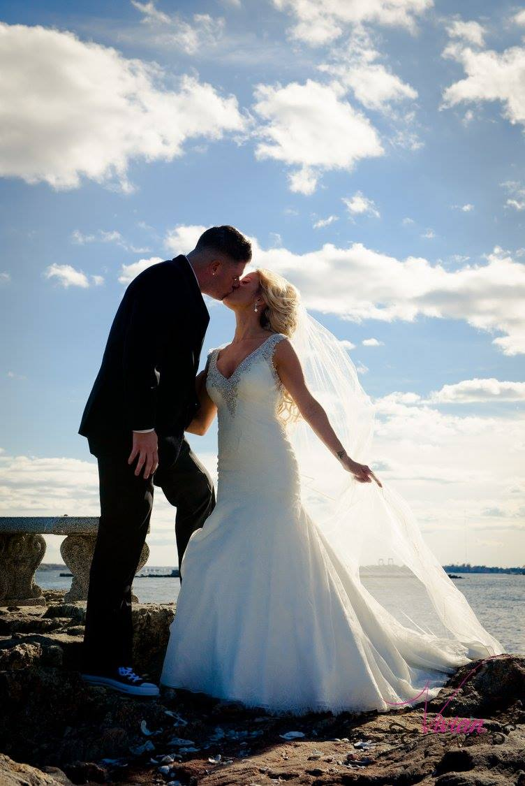 bride-and-groom-kissing-on-rocks-overlooking-water-with-blue-sky.jpg