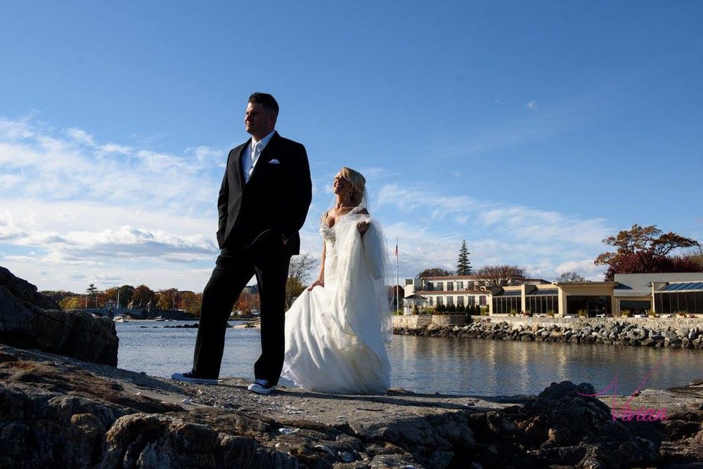 groom-looking-away-as-bride-approaches-from-behind-on-rocks-over-body-of-water.jpg