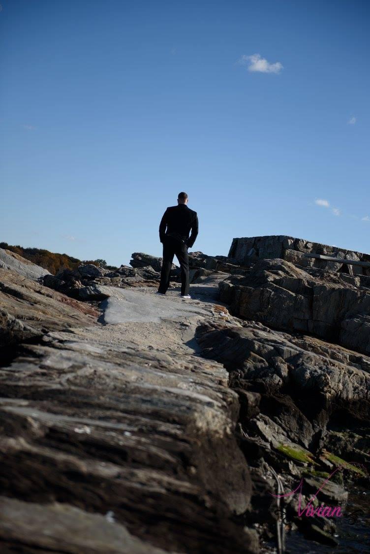 groom-standing-on-rocks-far-away-with-blue-sky.jpg
