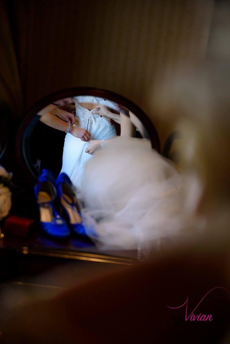 reflection-in-mirror-of-bridesmaids-zipping-brides-dress.jpg