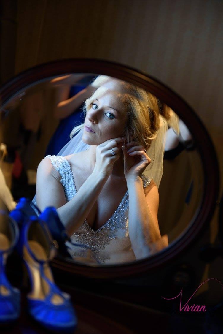 reflection-of-bride-putting-on-earrings-at-vanity.jpg