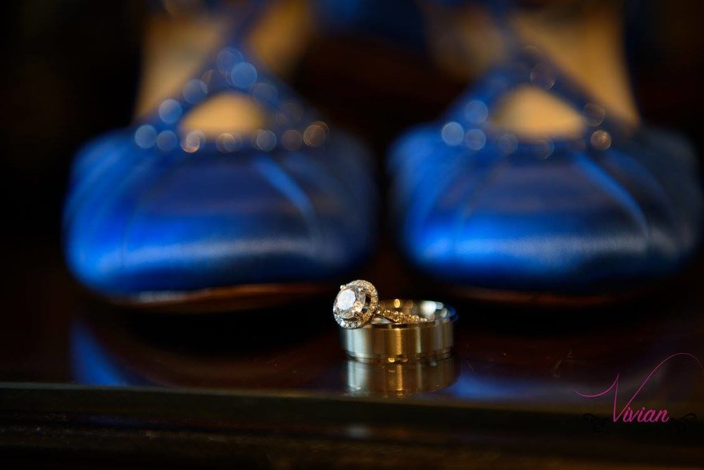 close-up-of-wedding-rings-with-blue-ballet-slippers-in-background.jpg