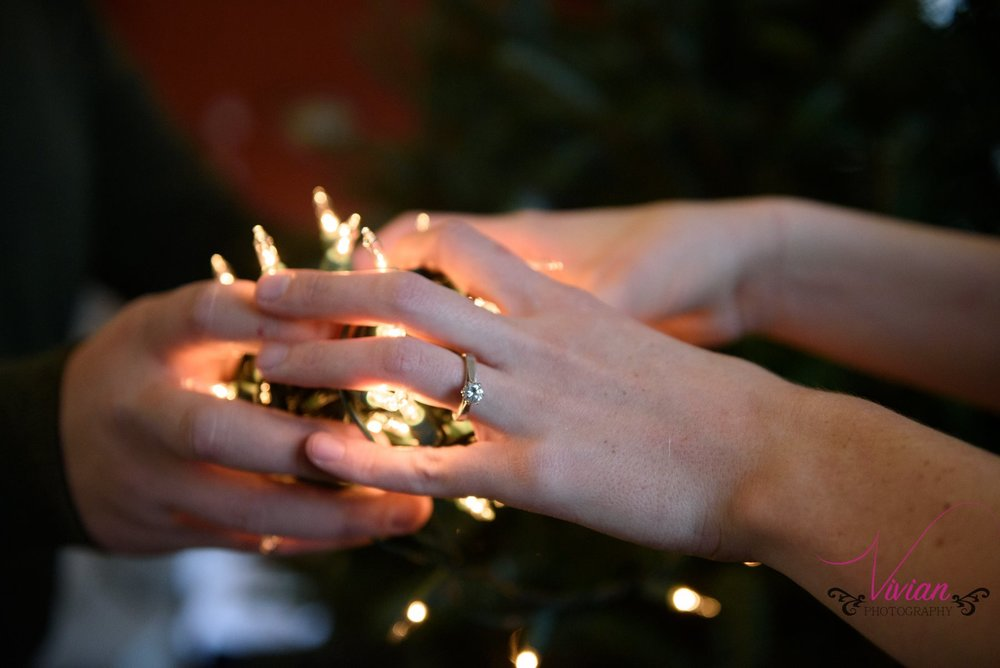 couple-clasping-christmas-lights-engagement-ring.jpg