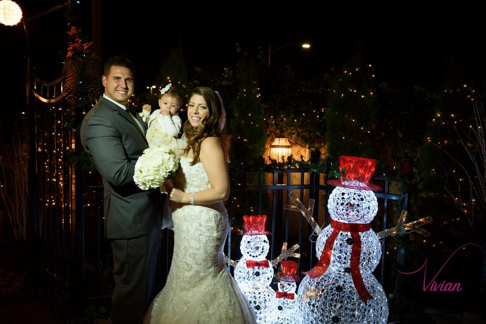bride-groom-holding-baby-posing-near-christmas-decorations.jpg
