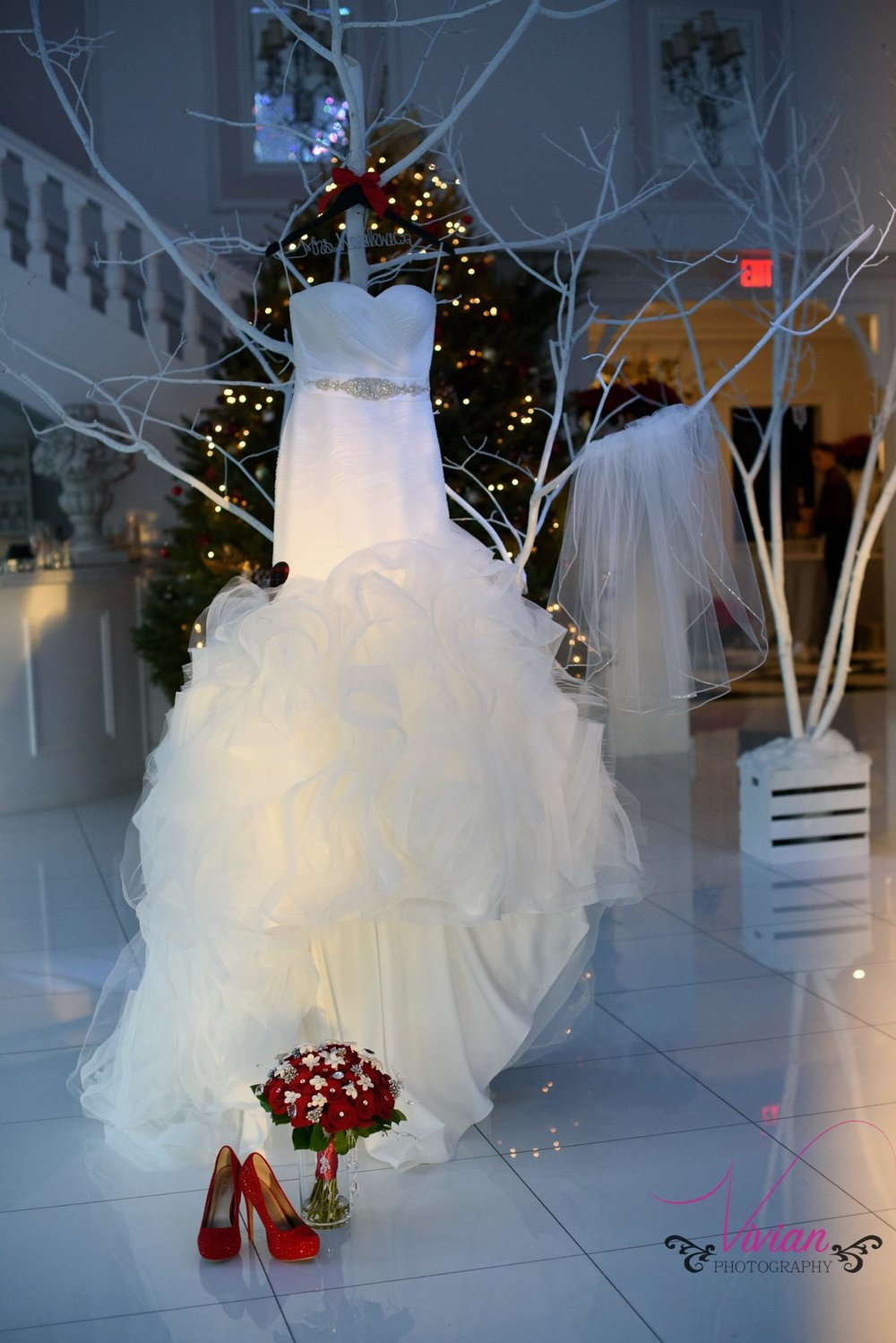 wedding-dress-hanging-from-white-tree-branches-near-red-heels.jpg