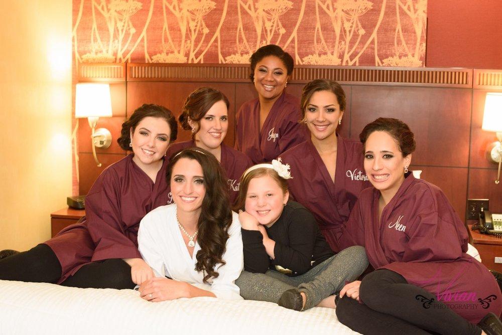 bridesmaids-in-robes-posing-on-bed.jpg