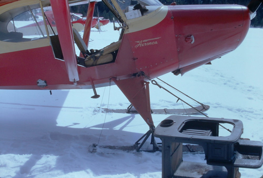 A MAINE WARDEN SERVICE AERONCA SEDAN READY TO HAUL A COOKSTOVE TO CLEAR LAKE CAMP