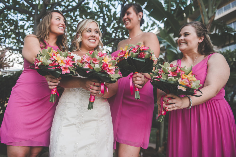 bride and bridesmaids pose with bouquets in maui