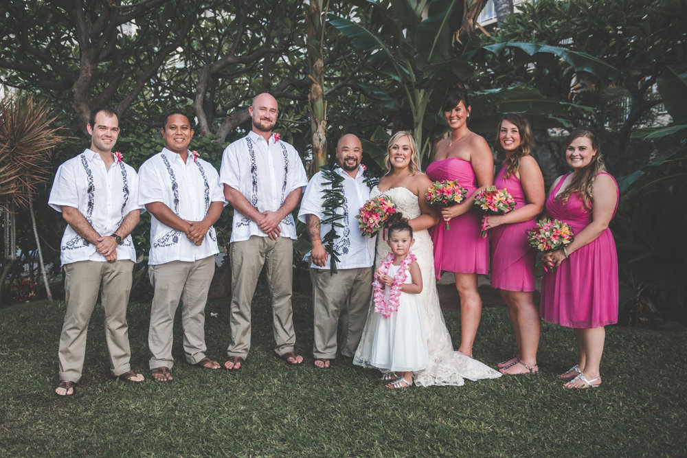 bride and groom pose with wedding court in maui