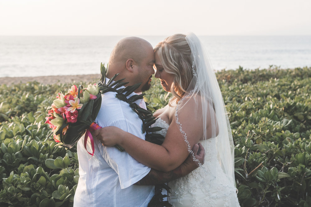 maui bride and groom embrace beachside