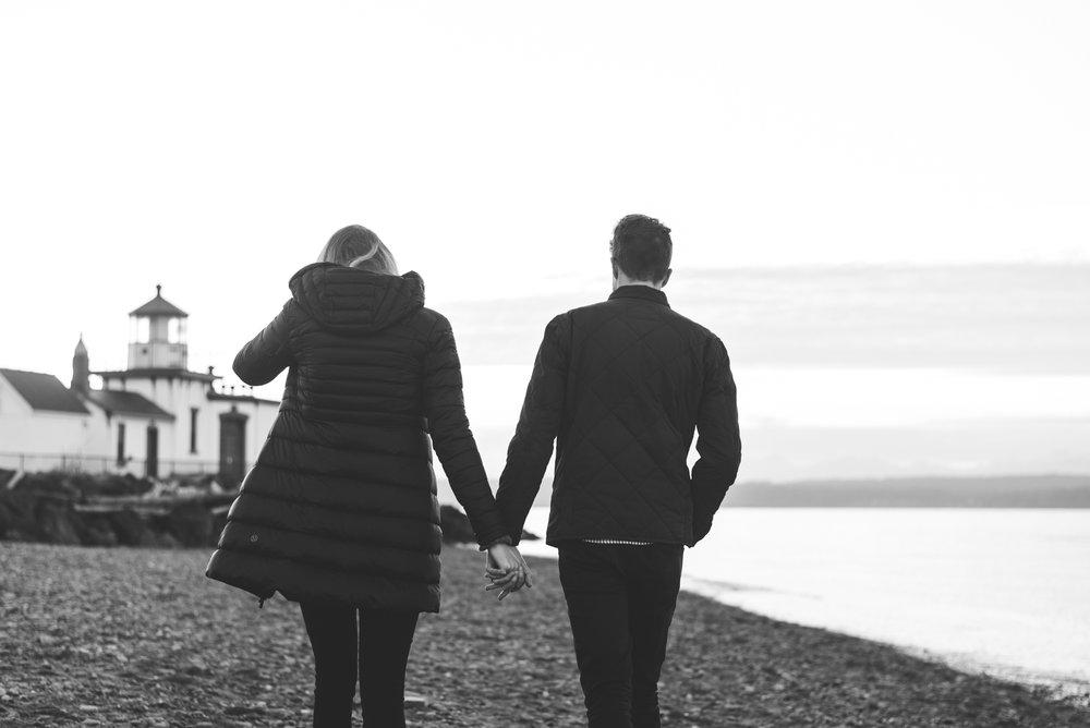 couple walk hand in hand on seattle beach in winter