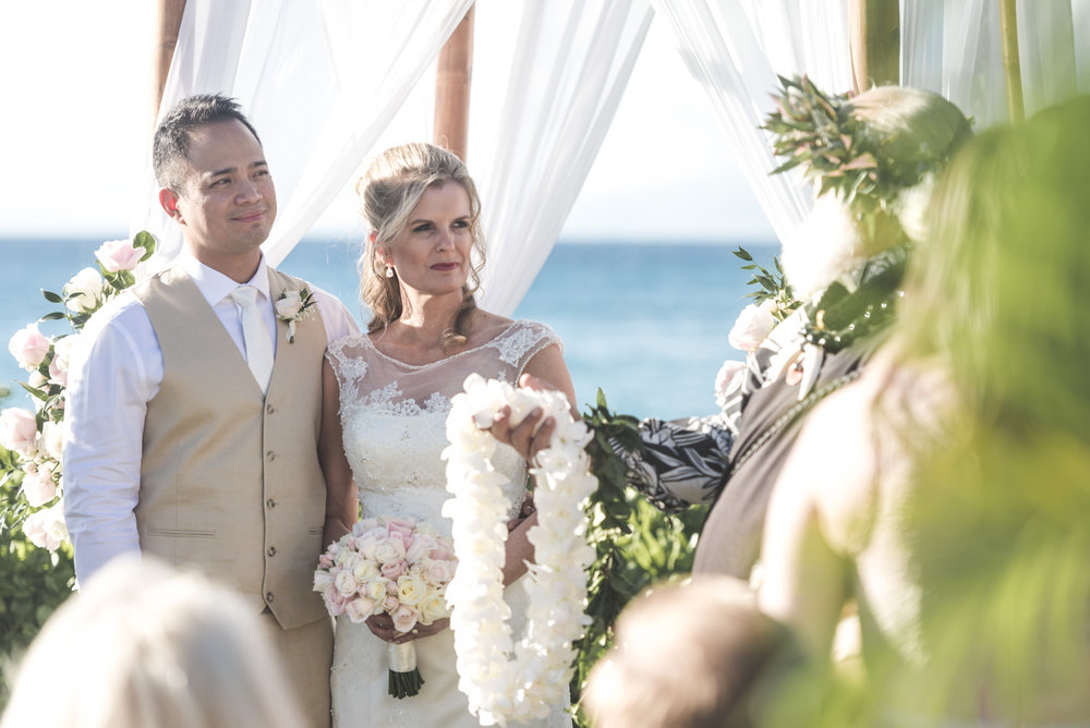 maui wedding minister offers flower lei to bride and groom
